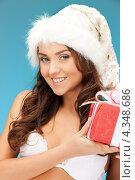 Купить «Счастливая девушка в шапке Санты-Клауса с новогодним подарком в руках», фото № 4348686, снято 2 апреля 2020 г. (c) Syda Productions / Фотобанк Лори