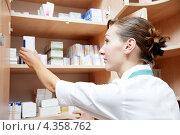 Купить «Женщина фармацевт берет лекарство с полки», фото № 4358762, снято 25 октября 2011 г. (c) Дмитрий Калиновский / Фотобанк Лори
