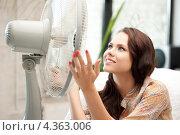 Купить «Счастливая молодая женщина сидит перед вентилятором», фото № 4363006, снято 16 июля 2011 г. (c) Syda Productions / Фотобанк Лори
