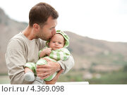 Купить «Счастливый отец держит на руках своего маленького сына и целует его», фото № 4369098, снято 8 октября 2010 г. (c) Andrejs Pidjass / Фотобанк Лори