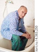 Купить «Мужчина-пациент в больничной пижаме сидит в санпропускнике больницы», фото № 4383250, снято 27 октября 2012 г. (c) Эдуард Паравян / Фотобанк Лори
