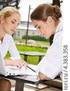 Купить «Две молодые сотрудницы обсуждают документы на свежем воздухе», фото № 4383358, снято 17 августа 2008 г. (c) Syda Productions / Фотобанк Лори