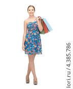 Купить «Довольная девушка в летнем платье с покупками в пакетах», фото № 4385786, снято 26 февраля 2012 г. (c) Syda Productions / Фотобанк Лори
