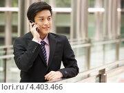 Китайский бизнесмен разговаривает по сотовому телефону. Стоковое фото, фотограф Monkey Business Images / Фотобанк Лори