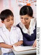 Китайский мальчик занимается с учительницей. Стоковое фото, фотограф Monkey Business Images / Фотобанк Лори