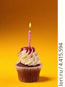 Купить «Шоколадный капкейк со свечкой на оранжевом фоне», фото № 4415594, снято 12 марта 2013 г. (c) Максим Бондарчук / Фотобанк Лори