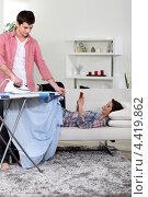 Купить «Молодой человек гладит одежду, а девушка отдыхает», фото № 4419862, снято 25 января 2011 г. (c) Phovoir Images / Фотобанк Лори