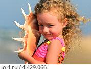 Купить «Кудрявая загорелая девочка с большой ракушкой на пляже», фото № 4429066, снято 15 июля 2012 г. (c) Эдуард Кислинский / Фотобанк Лори