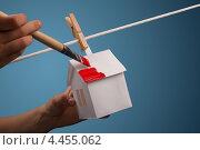 Бумажный домик, висящий на веревке, красят краской. Стоковое фото, фотограф Vycheslav Leskovskiy / Фотобанк Лори