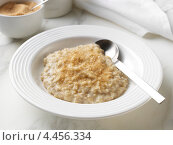 Купить «Белая тарелка с овсяной кашей посыпанной коричневым сахаром и ложкой», фото № 4456334, снято 22 апреля 2019 г. (c) Food And Drink Photos / Фотобанк Лори