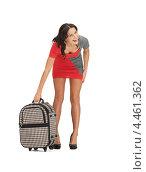 Привлекательная девушка с чемоданом на белом фоне готовится к туристической поездке. Стоковое фото, фотограф Syda Productions / Фотобанк Лори