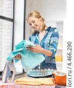 Купить «Довольная домохозяйка гладит утюгом дома белье», фото № 4466290, снято 17 июня 2012 г. (c) Syda Productions / Фотобанк Лори