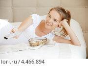 Красивая девушка с пультом дистанционного управления в руке и попкорном в миске. Стоковое фото, фотограф Syda Productions / Фотобанк Лори