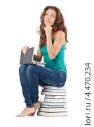 Купить «Девушка с ноутбуком на коленях сидит на стопке книг», фото № 4470234, снято 22 августа 2012 г. (c) Elnur / Фотобанк Лори