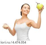 Купить «Молодая женщина выбирает между гамбургером и яблоком», фото № 4474054, снято 12 января 2013 г. (c) Syda Productions / Фотобанк Лори