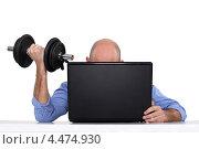 Купить «Деловой человек с гантелью за ноутбуком», фото № 4474930, снято 24 января 2011 г. (c) Phovoir Images / Фотобанк Лори