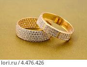 Купить «Два кольца с бриллиантами на золотом фоне», фото № 4476426, снято 10 мая 2012 г. (c) ElenArt / Фотобанк Лори