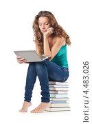 Купить «Грустная девушка с нетбуком сидит на стопке книг», фото № 4483026, снято 22 августа 2012 г. (c) Elnur / Фотобанк Лори