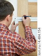 Купить «Плотник делает замеры двери», фото № 4484154, снято 16 декабря 2012 г. (c) Дмитрий Калиновский / Фотобанк Лори