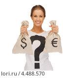 Купить «Юная девушка со светлыми волосами, убранными в косу, в футболке со знаком вопроса и с мешками евро и долларов в руках», фото № 4488570, снято 16 сентября 2012 г. (c) Syda Productions / Фотобанк Лори