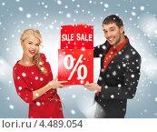Купить «Счастливая блондинка в красном платье и молодой человек в черном костюме на белом фоне со знаком скидки на распродаже», фото № 4489054, снято 7 октября 2012 г. (c) Syda Productions / Фотобанк Лори