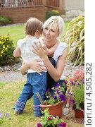Купить «Мама с дочерью обнимаются в летнем саду», фото № 4505282, снято 5 июня 2010 г. (c) Wavebreak Media / Фотобанк Лори
