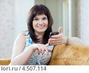 Женщина сидит на диване с мобильным телефоном. Стоковое фото, фотограф Яков Филимонов / Фотобанк Лори