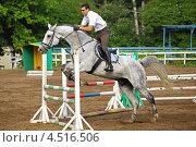 Купить «Жокей в очках и белой рубашке на лошади преодолевает барьер на ипподроме», фото № 4516506, снято 10 июня 2011 г. (c) Losevsky Pavel / Фотобанк Лори