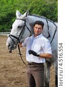 Купить «Мужчина жокей с лошадью на ипподроме», фото № 4516554, снято 10 июня 2011 г. (c) Losevsky Pavel / Фотобанк Лори