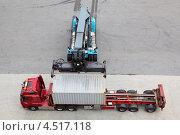 Купить «Кран движется и загружает контейнер в большой грузовик, вид сверху», фото № 4517118, снято 27 июля 2011 г. (c) Losevsky Pavel / Фотобанк Лори