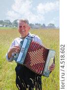 Купить «Счастливый пенсионер играет на гармошке в поле», фото № 4518602, снято 5 июля 2011 г. (c) Losevsky Pavel / Фотобанк Лори