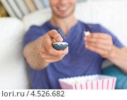 Купить «Рука с пультом от телевизора молодого человека, который ест попкорн», фото № 4526682, снято 9 июля 2010 г. (c) Wavebreak Media / Фотобанк Лори
