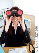 Купить «Девушка смотрит в офисе в бинокль, улыбаясь», фото № 4527366, снято 14 июля 2010 г. (c) Wavebreak Media / Фотобанк Лори