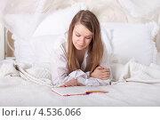 Молодая женщина читает книгу в постели. Стоковое фото, фотограф Дегтярева Виктория / Фотобанк Лори