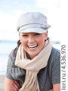 Купить «Девушка в кепке и шарфе на шее смеется на берегу моря», фото № 4536970, снято 17 сентября 2010 г. (c) Wavebreak Media / Фотобанк Лори