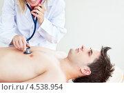 Купить «Молодой человек лежит на спине и его слушает доктор через стетоскоп», фото № 4538954, снято 29 мая 2010 г. (c) Wavebreak Media / Фотобанк Лори