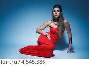 Красивая девушка в красном платье сидит на синем фоне. Стоковое фото, фотограф Михайлов Виталий / Фотобанк Лори