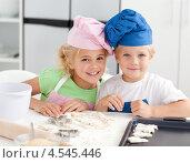Купить «Счастливые брат и сестра в поварских колпаках выкладывают пирожки на противне в кухне», фото № 4545446, снято 27 октября 2010 г. (c) Wavebreak Media / Фотобанк Лори