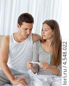 Купить «Мужчина смотрит на результаты теста на беременность рядом со своей подругой», фото № 4548022, снято 23 октября 2010 г. (c) Wavebreak Media / Фотобанк Лори