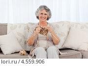 Купить «Пожилая улыбающаяся женщина вяжет на спицах сидя на диване», фото № 4559906, снято 31 октября 2010 г. (c) Wavebreak Media / Фотобанк Лори