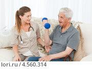 Купить «Медсестра помогает пожилому мужчине делать упражнения с гантелями», фото № 4560314, снято 31 октября 2010 г. (c) Wavebreak Media / Фотобанк Лори