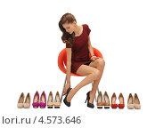 Купить «Юная девушка в красном платье выбирает туфли», фото № 4573646, снято 28 октября 2012 г. (c) Syda Productions / Фотобанк Лори