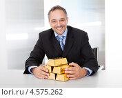 Купить «Довольный бизнесмен за столом с золотыми слитками», фото № 4575262, снято 22 апреля 2012 г. (c) Андрей Попов / Фотобанк Лори