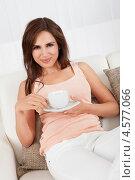 Купить «Красивая молодая брюнетка пьет кофе, удобно устроившись на диване», фото № 4577066, снято 7 июня 2012 г. (c) Андрей Попов / Фотобанк Лори