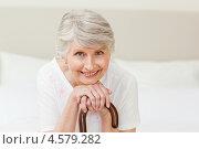 Купить «Улыбающаяся пожилая женщина сидит, облокотившись на палочку», фото № 4579282, снято 6 ноября 2010 г. (c) Wavebreak Media / Фотобанк Лори