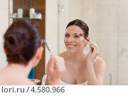 Купить «Девушка подкрашивает брови в ванной комнате, стоя напротив зеркала», фото № 4580966, снято 7 ноября 2010 г. (c) Wavebreak Media / Фотобанк Лори