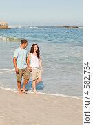 Молодая влюбленная пара идет по пустынному пляжу вдоль моря. Стоковое фото, агентство Wavebreak Media / Фотобанк Лори