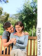 Купить «Молодой мужчина дарит темноволосой девушке цветок герберы в летнем парке», фото № 4585842, снято 15 ноября 2010 г. (c) Wavebreak Media / Фотобанк Лори