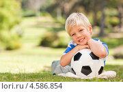 Улыбающийся светловолосый мальчик с футбольным мячом лежит на траве в парке в солнечную погоду. Стоковое фото, агентство Wavebreak Media / Фотобанк Лори