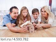 Купить «Мама, папа, сын и дочь строят дом из деревянных кубиков, лежа на полу», фото № 4593782, снято 8 июля 2012 г. (c) Андрей Попов / Фотобанк Лори